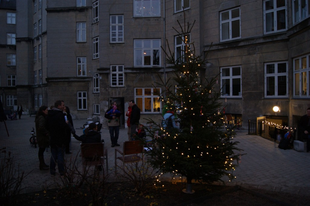 Folk snakker og hygger mens de kigger paa de smukke lys i juletraeet 2011