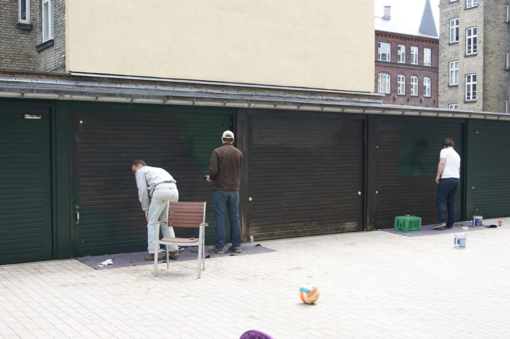Tre af de frivillige er i gang med at male et lag Frederiksberg-grønne