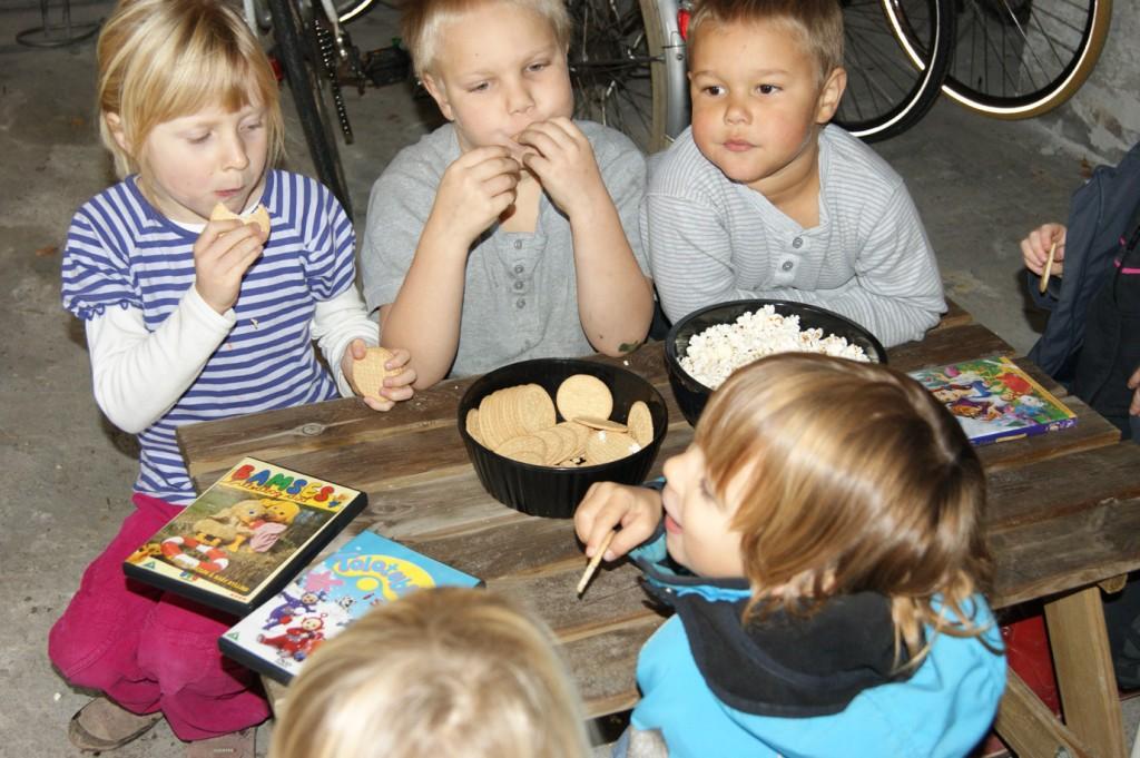 Børnene nyder småkager og popcorn i børnebiografen.