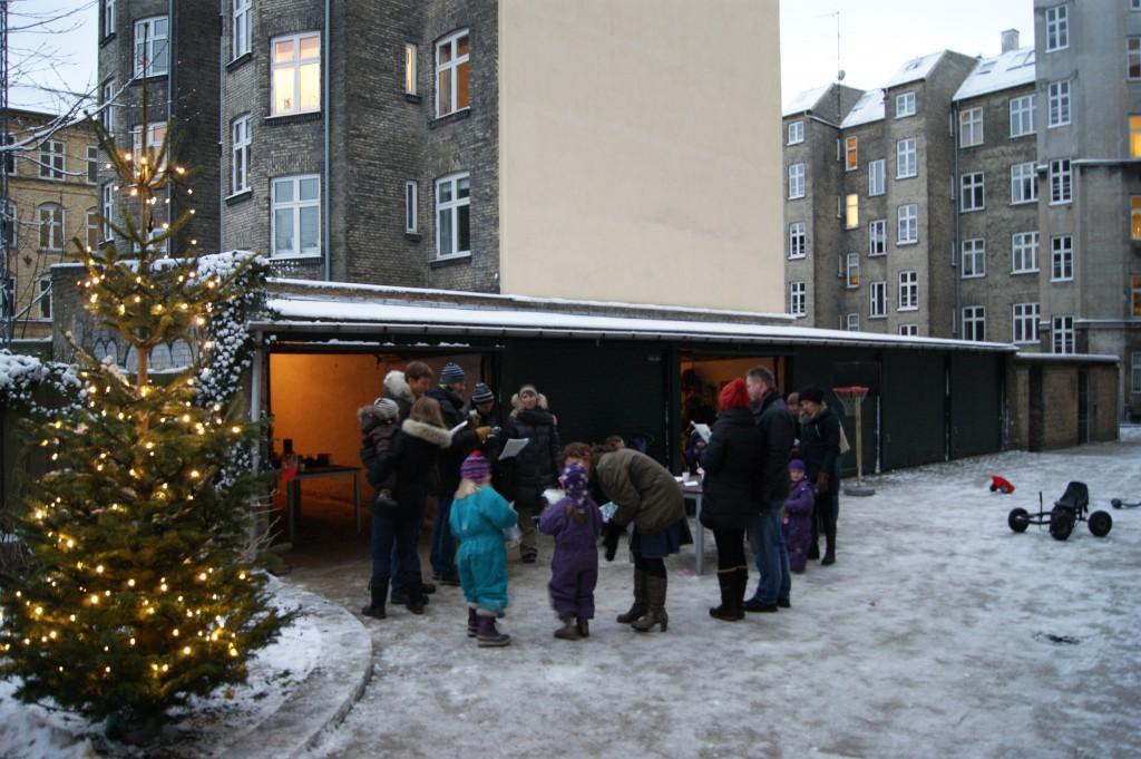 Folk står og synger julesang ved siden af det tændte juletræ