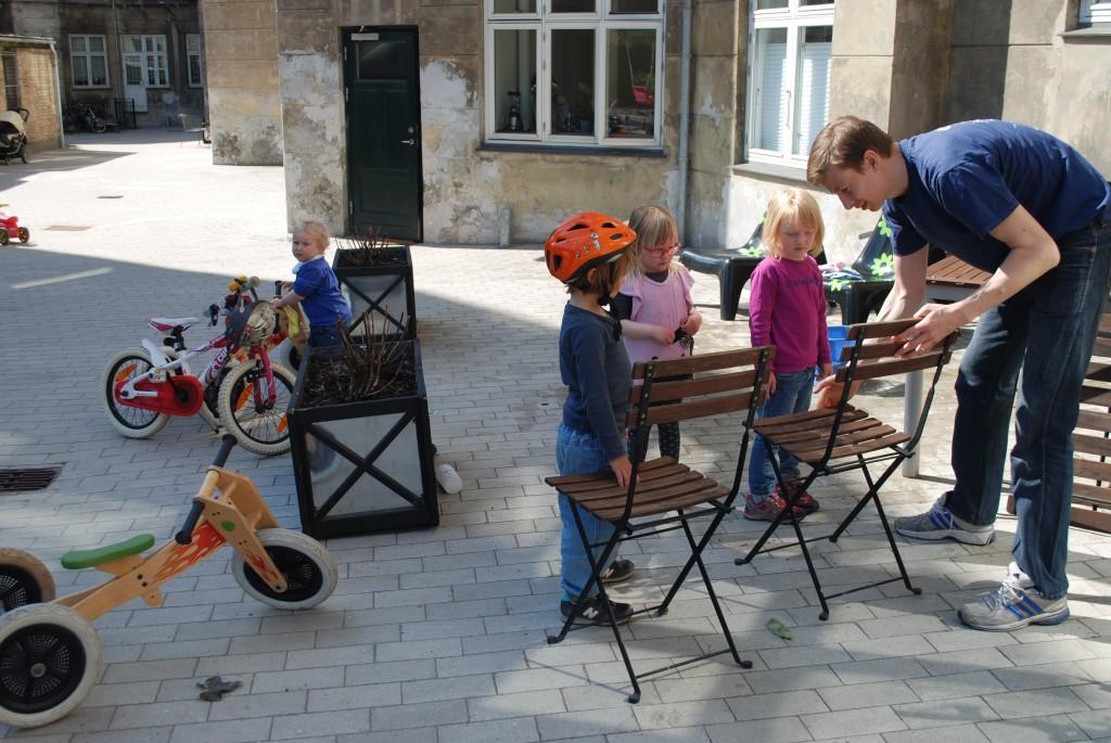 3 børn inspicerer en fars arbejde med stolene, mens et andet barn knokler med en cykel i baggrunden.