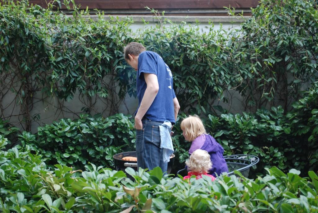 En far og 2 unge medhjælpere passer pølserne på grillen.