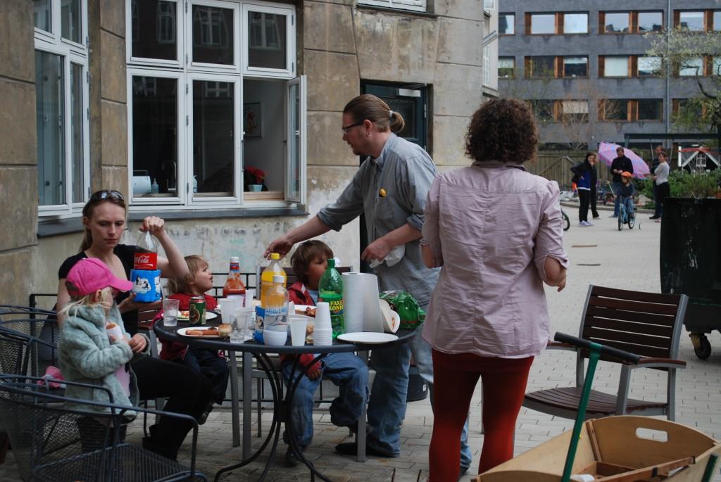 Voksne og unge slukker tørst og hviler omkring et bord, mens andre cykler og snakker i baggrunden.