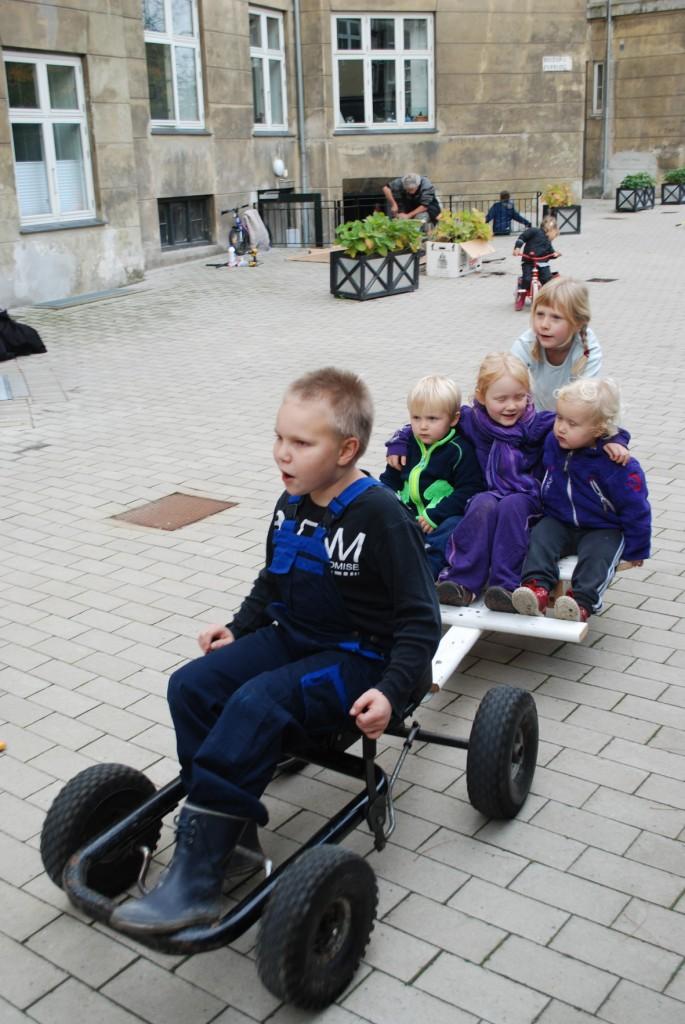 En dreng kører go-kart med 4 børn på slæb.