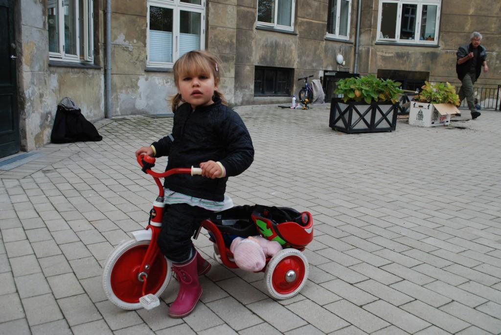 En pige på en tre-hjulet cykel kigger på fotografen.