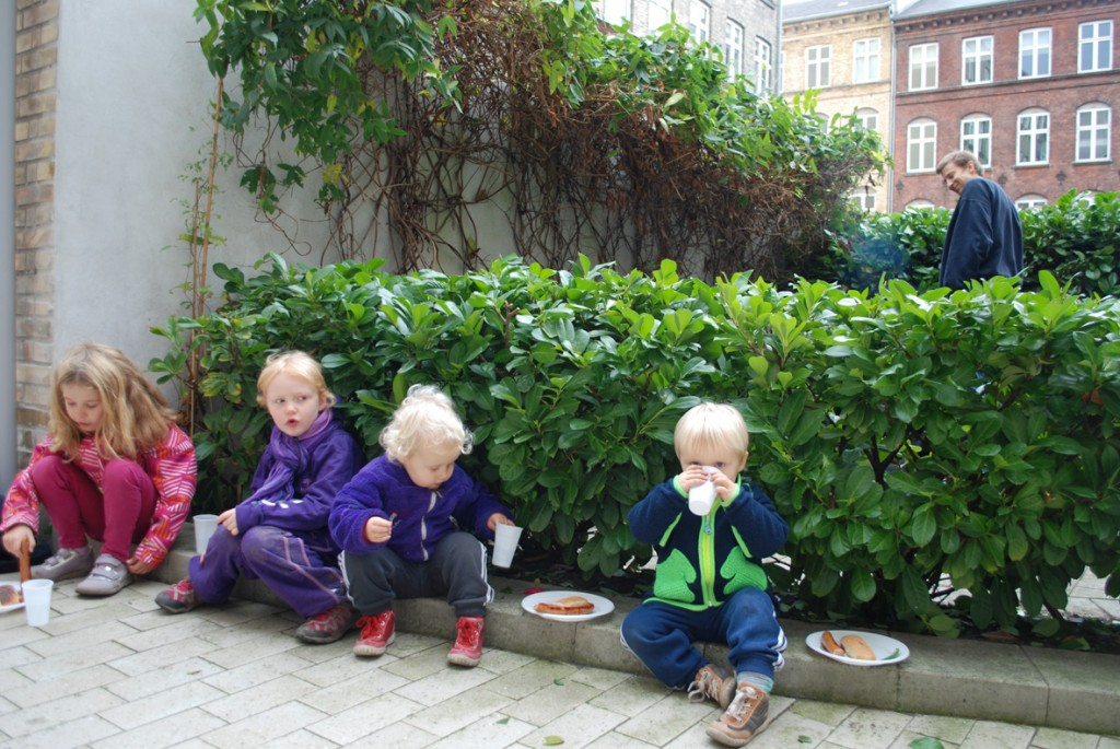 4 børn nyder pølser med brød og saft på kantstenen i gården.