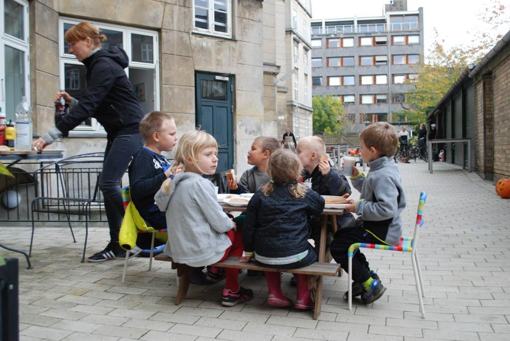 6 børn sidder ved havebordet og venter på en mor til at skænke sodavand.