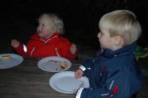 En glad lille pige og en dreng har spist deres æbleskiver